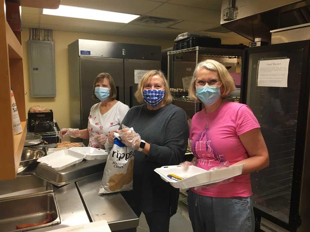 Shirley Dillard, Kerri Dodd, and Kathy Crowe prepare to-go meals at the Cornelia Soup Kitchen.